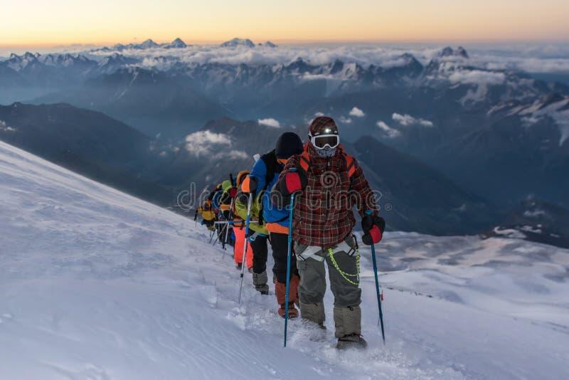 Η ομάδα ορειβατών στα βουνά πηγαίνει στην κορυφή στοκ φωτογραφία