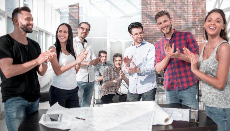 Η ομάδα σχεδίου έδωσε μια όρθια επευφημία στο δημιουργικό γραφείο στοκ εικόνα με δικαίωμα ελεύθερης χρήσης