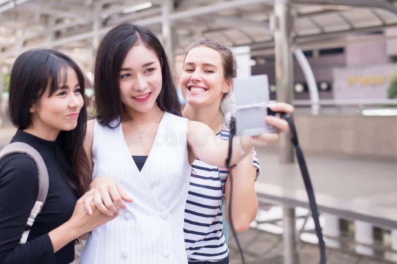 Η ομάδα ταξιδιώτη γυναικών κάνει το selfie της στην κεντρική οδό, όμορφο θηλυκό που περπατά στις οδούς, ευτυχής και που χαμογελά στοκ φωτογραφία με δικαίωμα ελεύθερης χρήσης