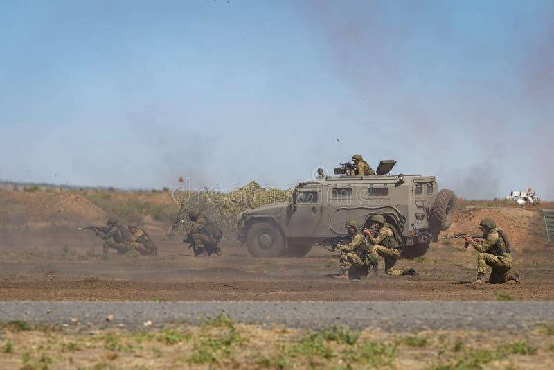 Η ομάδα των οπλισμένων στρατιωτών μαζί με ένα θωρακισμένο αυτοκίνητο στο πεδίο μάχη υπερασπίζει τις θέσεις τους στοκ εικόνα