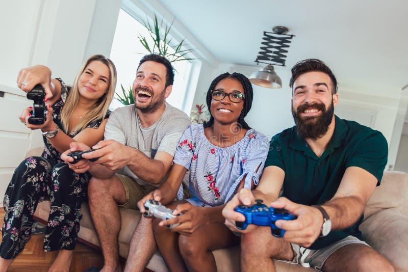 Η ομάδα φίλων παίζει τα τηλεοπτικά παιχνίδια στοκ φωτογραφίες