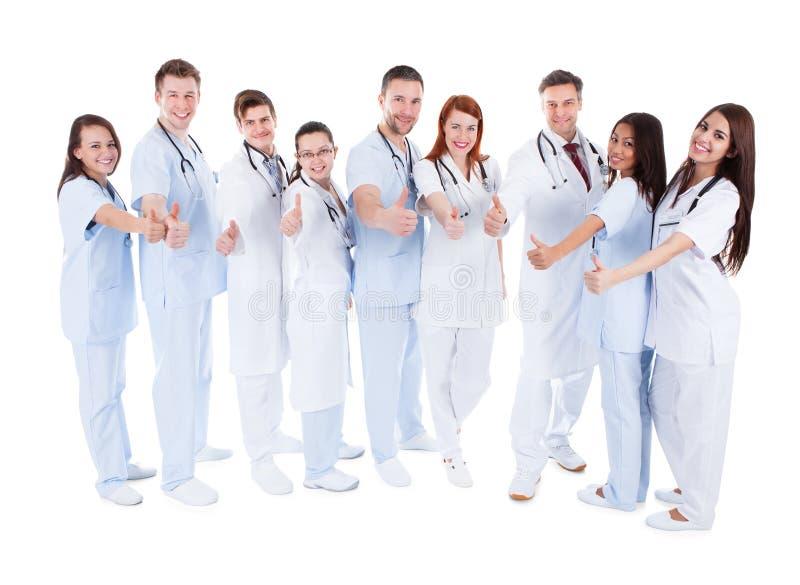 Η ομάδα εύθυμης παρουσίασης γιατρών φυλλομετρεί επάνω στοκ εικόνες