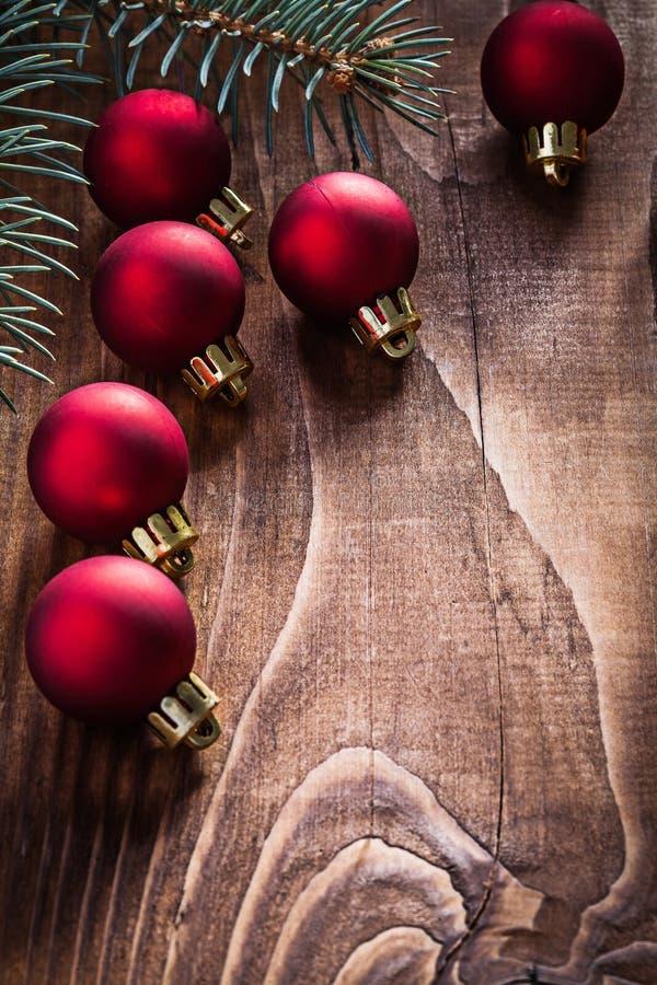 Η ομάδα κόκκινων μπιχλιμπιδιών Χριστουγέννων και ο κλάδος του δέντρου έλατου σε παλαιό επιζητούν στοκ φωτογραφία με δικαίωμα ελεύθερης χρήσης