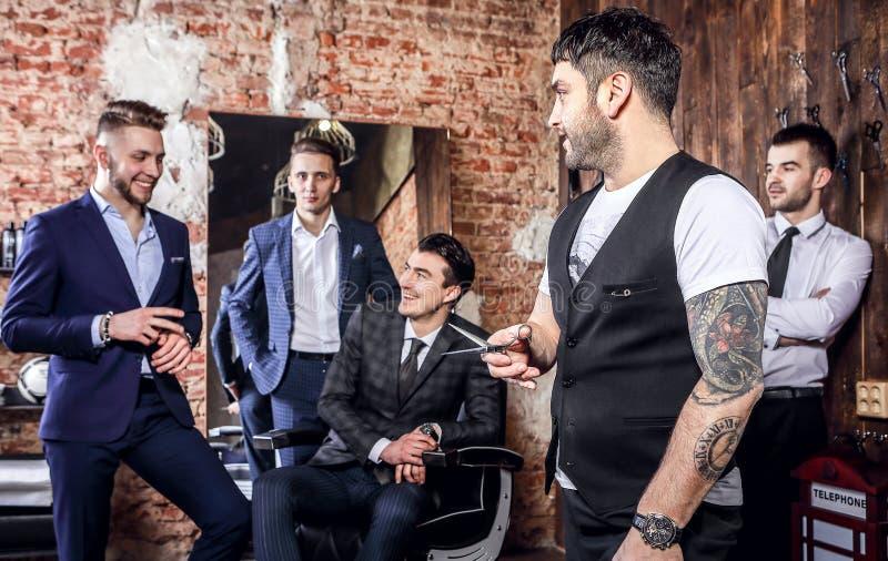 Η ομάδα νέων κομψών θετικών ατόμων θέτει στο εσωτερικό του barbershop στοκ φωτογραφία