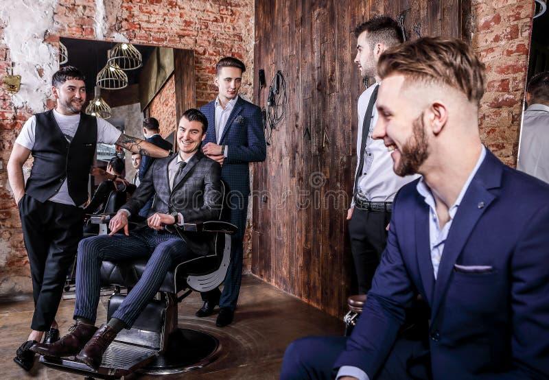 Η ομάδα νέων κομψών θετικών ατόμων θέτει στο εσωτερικό του barbershop στοκ φωτογραφία με δικαίωμα ελεύθερης χρήσης