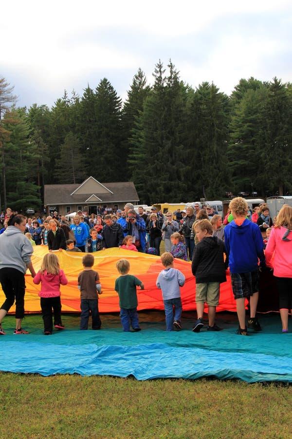 Η ομάδα παιδιών και νέων ενηλίκων που βοηθούν να ξεδιπλώσει τα μπαλόνια στο ετήσιο φεστιβάλ, πάρκο Crandall, Glens πέφτει, Νέα Υό στοκ φωτογραφία με δικαίωμα ελεύθερης χρήσης