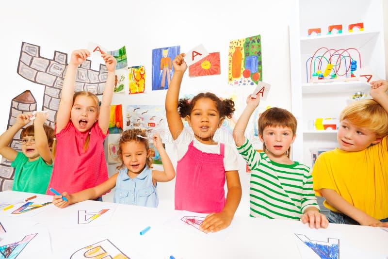 Η ομάδα παιδιών μαθαίνει τις πρώτες επιστολές στην κατηγορία ανάγνωσης στοκ φωτογραφία