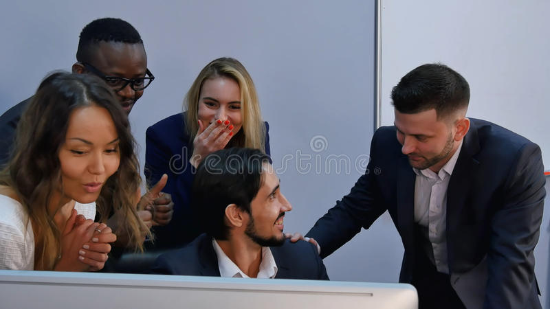 Η ομάδα πολυφυλετικής επιχειρησιακής ομάδας με το αποτέλεσμα, έκπληκτο, που χαμογελά και που εξετάζει το φορητό προσωπικό υπολογι στοκ εικόνες
