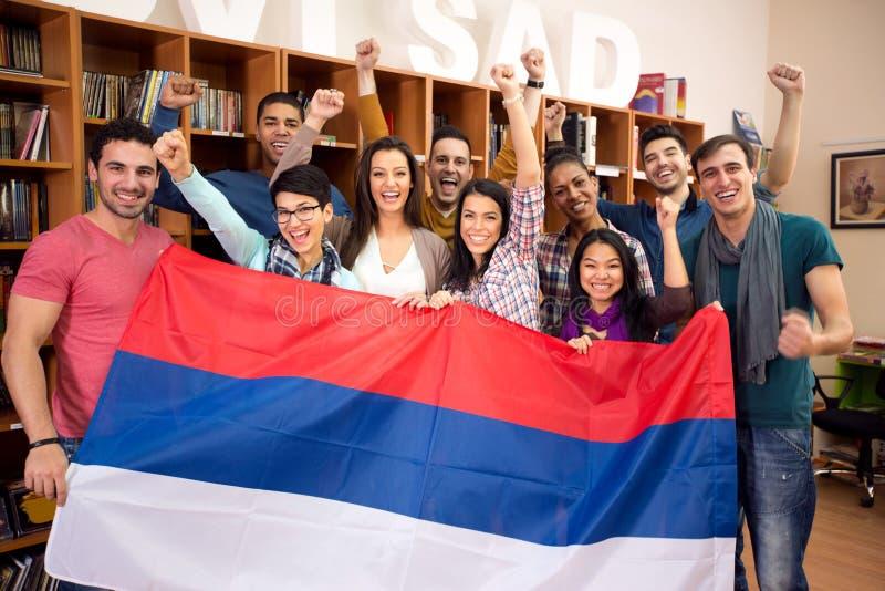 Η ομάδα σπουδαστών κρατά τη σερβική σημαία και τις αυξημένες πυγμές νίκης στοκ εικόνες