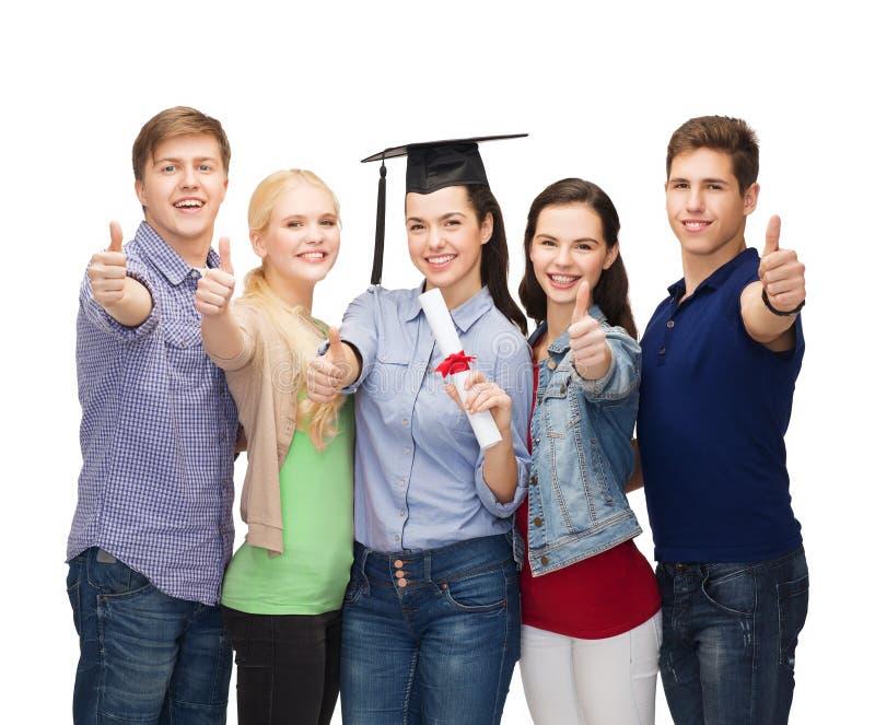 Η ομάδα σπουδαστών με την παρουσίαση διπλωμάτων φυλλομετρεί επάνω στοκ εικόνες