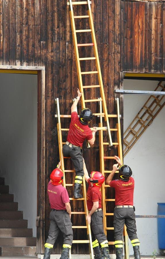 Η ΟΜΑΔΑ των πυροσβεστών κατά τη διάρκεια του τρυπανιού πυρκαγιάς τοποθετεί τη γρήγορη ξύλινη σκάλα στοκ φωτογραφία