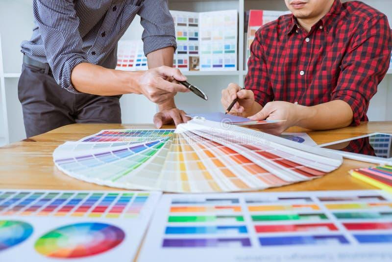 Η ομαδική εργασία των νέων δημιουργικών σχεδιαστών που εργάζονται στο πρόγραμμα μαζί και επιλέγει swatch χρώματος τα δείγματα για στοκ εικόνες με δικαίωμα ελεύθερης χρήσης