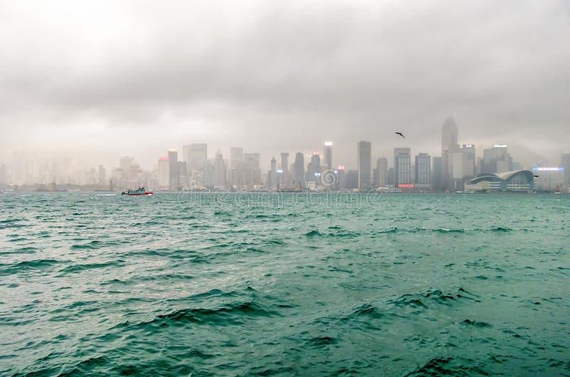 Η ομιχλώδης εικονική παράσταση πόλης Χονγκ Κονγκ πέρα από το θυελλώδες λιμάνι Βικτώριας είναι ένα κοινό τοπίο της πόλης στοκ εικόνα με δικαίωμα ελεύθερης χρήσης