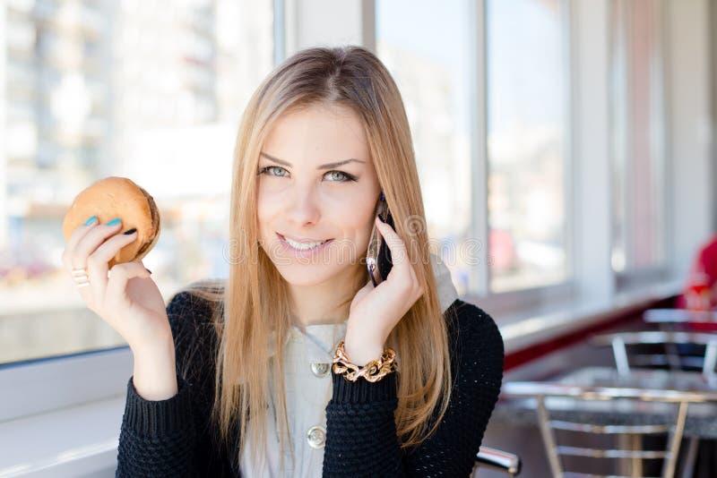 Η ομιλία στο κινητό κύτταρο τηλεφωνούν και η κατοχή του μεσημεριανού γεύματος όμορφη νέα επιχειρησιακή γυναίκα ευτυχές χαμόγελο ε στοκ εικόνες