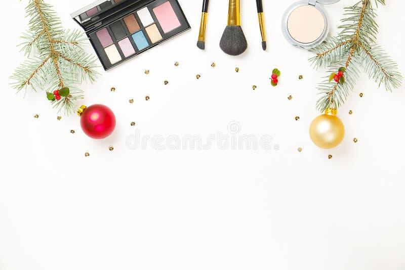 Η ομορφιά καθιστά επάνω το καλλυντικό τεθειμένο ως στόχος με τη διακόσμηση και το παρόν Χριστουγέννων στο επίπεδο χεριών γυναικών στοκ εικόνες