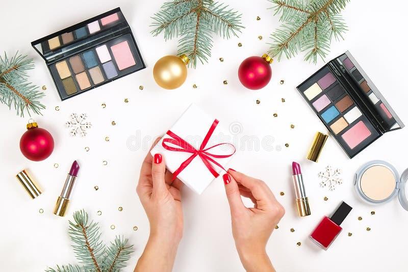 Η ομορφιά καθιστά επάνω το καλλυντικό τεθειμένο ως στόχος με τη διακόσμηση και το παρόν Χριστουγέννων στο επίπεδο χεριών γυναικών στοκ φωτογραφία