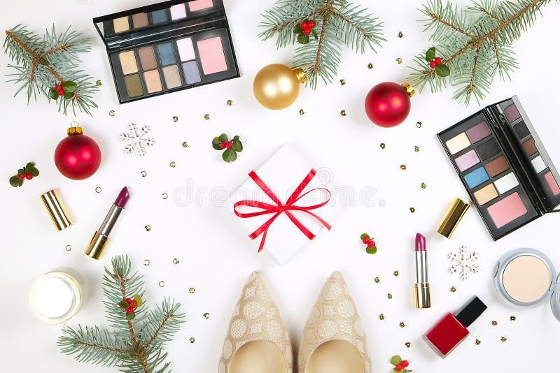 Η ομορφιά καθιστά επάνω το καλλυντικό τεθειμένο ως στόχος με τη διακόσμηση και το παρόν Χριστουγέννων στο επίπεδο χεριών γυναικών στοκ φωτογραφίες