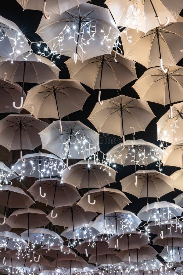 Η ομορφιά των άσπρων ομπρελών που φωτίζονται από τα φω'τα Χριστουγέννων που διακοσμούν τις οδούς Agueda Πορτογαλία στοκ φωτογραφία