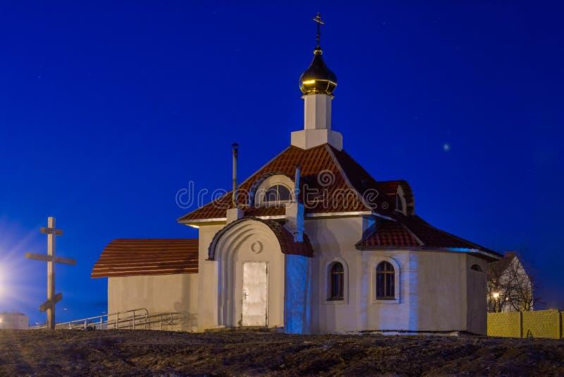 Η ορθόδοξη χριστιανική εκκλησία με έναν χρυσό θόλο τη νύχτα ανάβει από ένα επίκεντρο, ένας ξύλινος σταυρός θάβεται στο έδαφος στοκ εικόνα