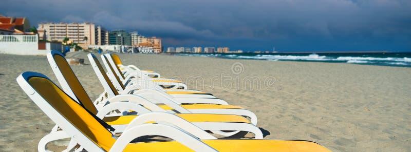 Η οριζόντια εικόνα καλλιέργησε άποψης τις κίτρινες μπλε γέφυρα-καρέκλες sunbeds χρώματος κενές σε μια σειρά στην αμμώδη παραλία,  στοκ φωτογραφία