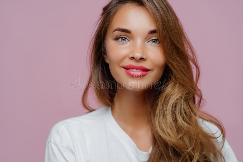 Η οριζόντια εικόνα του ευχάριστου γυναικείου μοντέλου έχει τρυφερό χαμόγελο, φοράει ελάχιστο μακιγιάζ, έχει μακριά κυματιστά μαλλ στοκ εικόνα