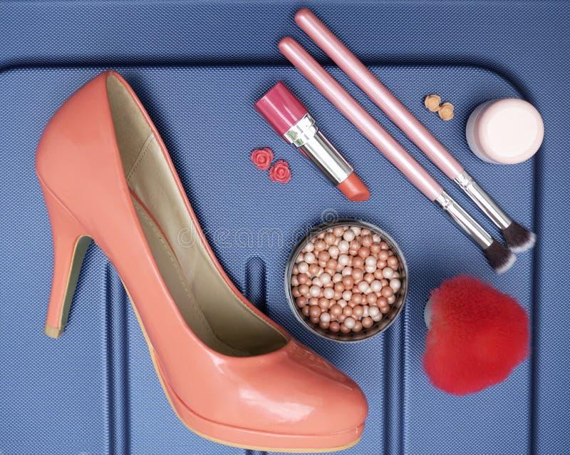 Η ουσία γυναικών, αποτελεί το προϊόν και το παπούτσι στο μπλε υπόβαθρο Εξαρτήματα ταξιδιού στοκ φωτογραφία με δικαίωμα ελεύθερης χρήσης