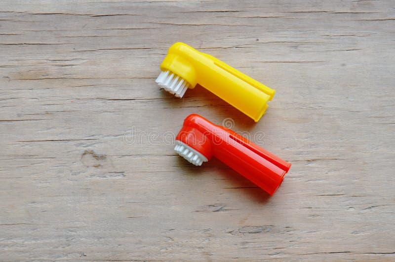 Η οδοντόβουρτσα χρησιμοποιούμενη κοντά υπόβαλε το δάχτυλο για το σκυλί και τη γάτα στον ξύλινο πίνακα στοκ εικόνες με δικαίωμα ελεύθερης χρήσης