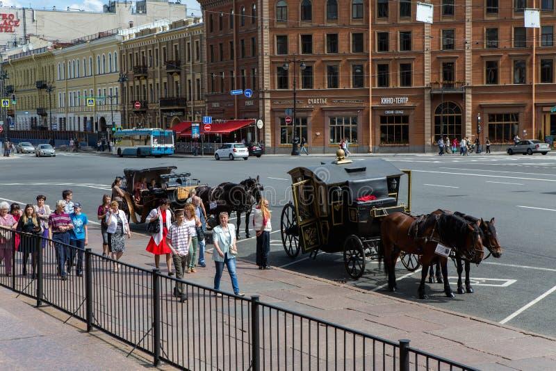 Η οδός σε Άγιο Πετρούπολη από τον καθεδρικό ναό του ST Isaac, άνθρωποι πηγαίνει, οι τουρίστες είναι άλογα με τις μεταφορές στοκ φωτογραφία