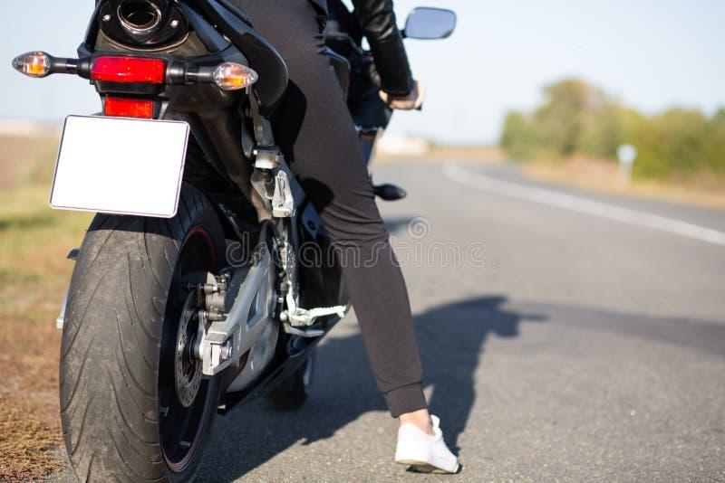 Η πίσω άποψη της απρόσωπης συνεδρίασης γυναικών στο μαύρο γρήγορο motobike, θηλυκά ταξίδια μόνο, παίρνει το σπάσιμο μετά από τις  στοκ εικόνες με δικαίωμα ελεύθερης χρήσης