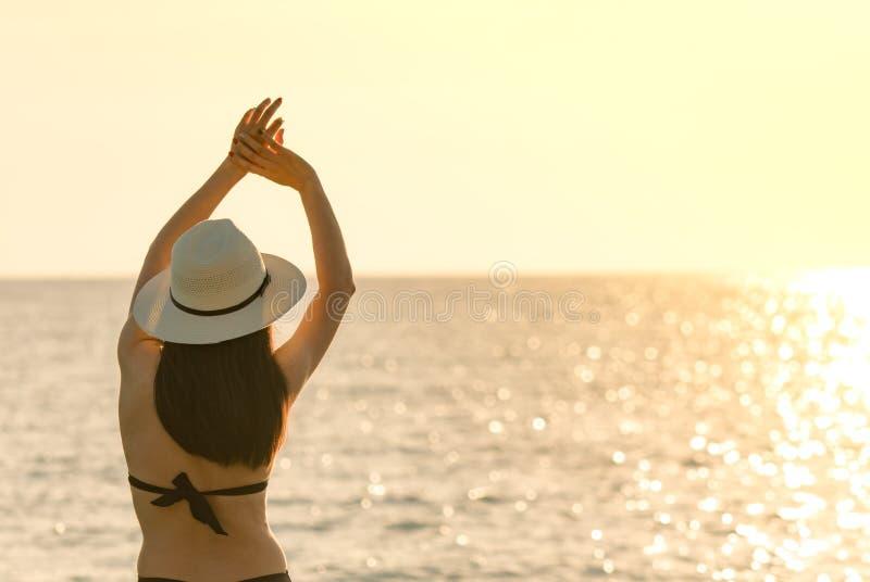 Η πίσω άποψη της ευτυχούς νέας ασιατικής γυναίκας στο μαύρο καπέλο μαγιό και αχύρου χαλαρώνει και απολαμβάνει τις διακοπές στην τ στοκ φωτογραφία με δικαίωμα ελεύθερης χρήσης