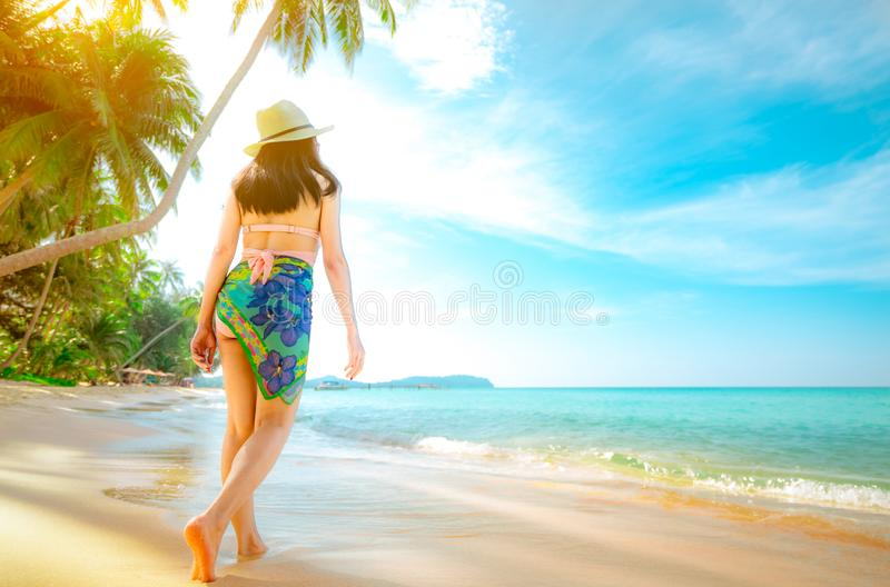 Η πίσω άποψη της ευτυχούς νέας ασιατικής γυναίκας στο ρόδινο καπέλο μαγιό και αχύρου χαλαρώνει και απολαμβάνει τις διακοπές στην  στοκ φωτογραφία με δικαίωμα ελεύθερης χρήσης