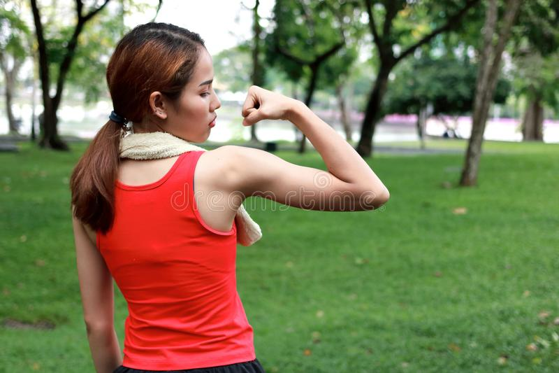 Η πίσω άποψη της υγιούς ισχυρής ασιατικής γυναίκας κόκκινο sportswear που παρουσιάζει την παραδίδει το φυσικό πάρκο Έννοια ικανότ στοκ εικόνα