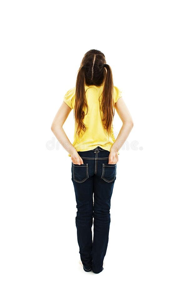 Η πίσω άποψη του μικρού κοριτσιού και με τους δύο παραδίδει τις τσέπες της εξετάζοντας επάνω τον τοίχο στοκ εικόνες