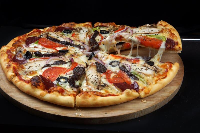 Η πίτσα κρέατος με το κοτόπουλο, το βόειο κρέας, το σαλάμι και το μπέϊκον, περικοπή στα κομμάτια βρίσκονται στον πίνακα, το ένα κ στοκ φωτογραφία με δικαίωμα ελεύθερης χρήσης