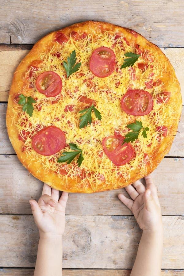 Η πίτσα της Μαργαρίτα με το τυρί και οι ντομάτες στον ξύλινο πίνακα, χέρια παιδιών έχουν την πίτσα, τη τοπ άποψη και τη θέση για  στοκ εικόνες με δικαίωμα ελεύθερης χρήσης