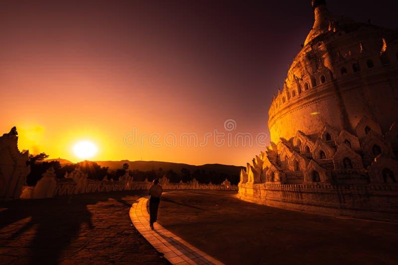 Η παγόδα Hsinbyume στη γυναίκα τουριστών Mingun το Μιανμάρ περπατά προς το όμορφο ηλιοβασίλεμα στοκ φωτογραφία