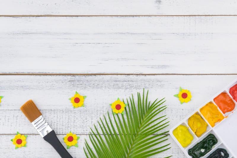 Η παλέτα και το πινέλο Watercolor διακοσμούν με τα φύλλα φτερών και τα κίτρινα λουλούδια εγγράφου στοκ εικόνα