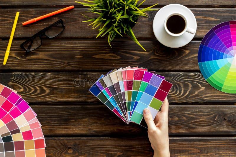 Η παλέτα στα χέρια, τα μολύβια, τα γυαλιά, το φλιτζάνι του καφέ και τα εργαλεία για το σχεδιαστή λειτουργούν στην ξύλινη τοπ άποψ στοκ εικόνα με δικαίωμα ελεύθερης χρήσης