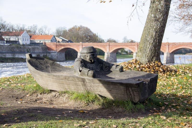 Η παλαιά γέφυρα τούβλου πέρα από τον ποταμό Venta στην πόλη Kuldiga Λετονία και ο ξύλινος ψαράς στη βάρκα λογαριάζουν στο μέτωπο στοκ εικόνα με δικαίωμα ελεύθερης χρήσης