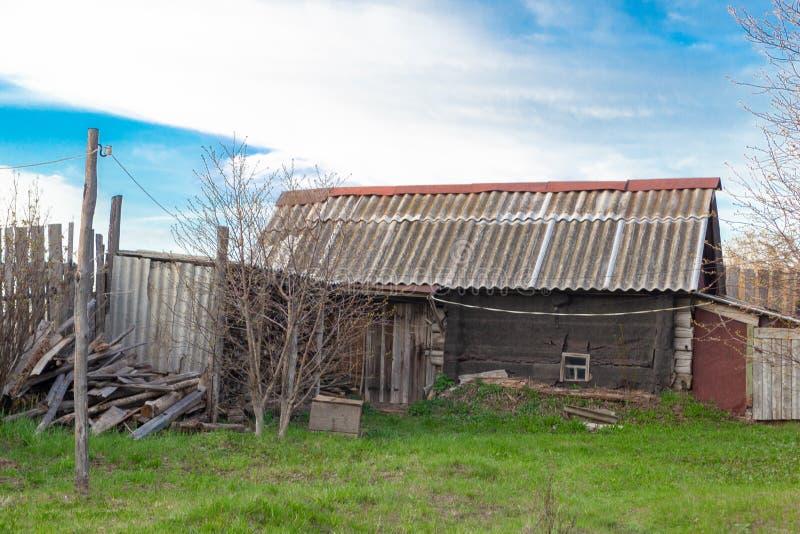 Η παλαιά ξεχαρβαλωμένη ξύλινη καλύβα από τα κούτσουρα με μια στέγη που καλύπτεται με την πλάκα Ρωσικό σπιτικό λουτρό χωρών στοκ φωτογραφία με δικαίωμα ελεύθερης χρήσης