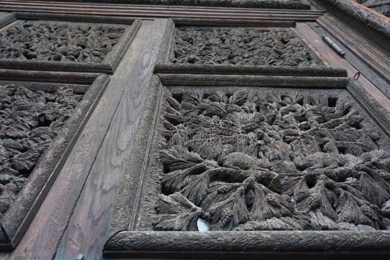 Η παλαιά ξύλινη γλυπτική αυλακώματος ματαιώνει τα κίνητρα στις πόρτες στοκ φωτογραφία