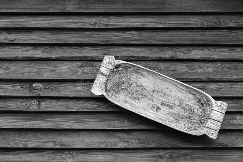 Η παλαιά ξύλινη λεκάνη για την πλύση ή μια γούρνα σίτισης κρεμά σε έναν ξύλινο τοίχο στοκ φωτογραφίες