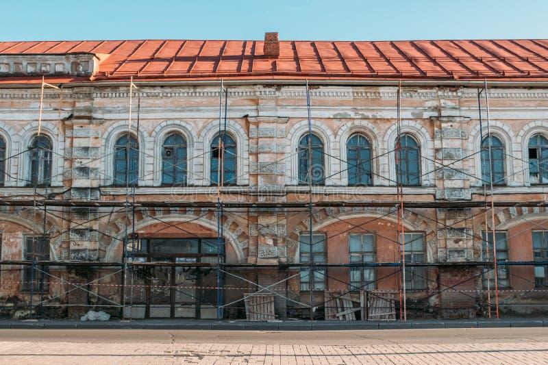 Η παλαιά οικοδόμησης έννοια αποκατάστασης προσόψεων εξωτερική ή ανακαίνισης ή αναδημιουργίας σπιτιών, τα υλικά σκαλωσιάς και η επ στοκ φωτογραφία