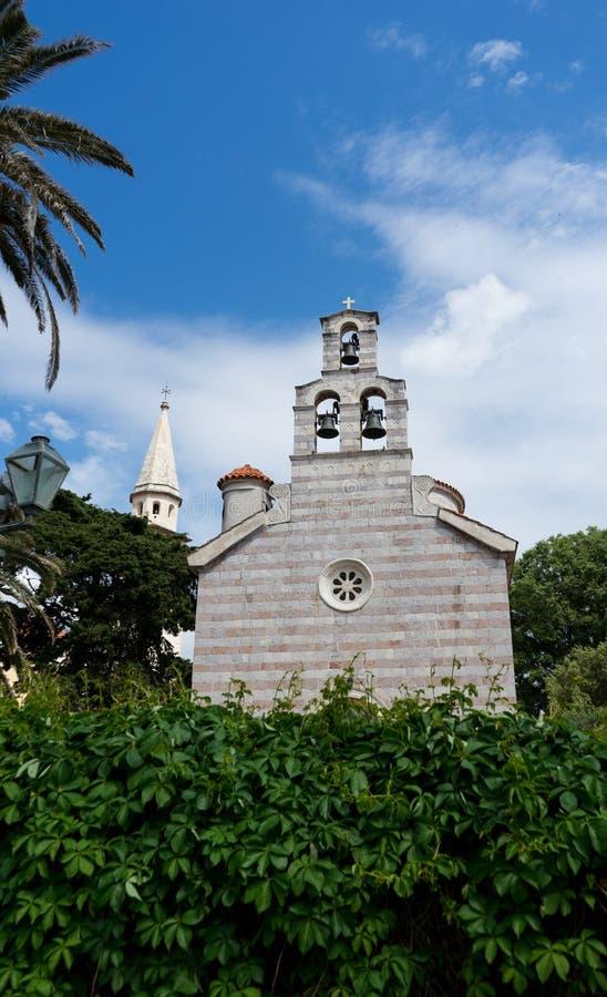 Η παλαιά πόλη Budva, Μαυροβούνιο - μια παλαιά εκκλησία πετρών που εμμένει στο φρούριο Budva στην αδριατική θάλασσα Λουλούδια και  στοκ εικόνες με δικαίωμα ελεύθερης χρήσης