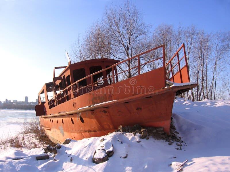 Η παλαιά σκουριασμένη βάρκα που δέθηκε στην ακτή το χειμώνα επάγωσε στον ποταμό στοκ εικόνες