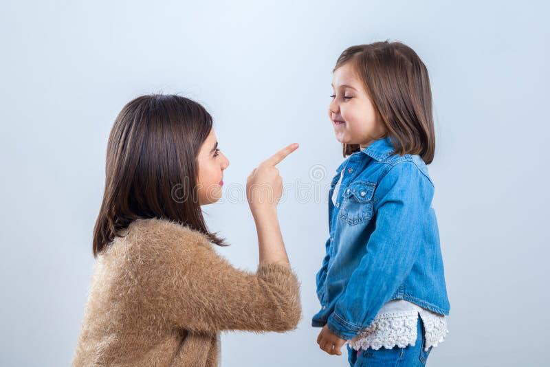 Η παλαιότερη αδελφή δίνει μια παρατήρηση στη νεώτερη με ένα δάχτυλο στοκ εικόνες