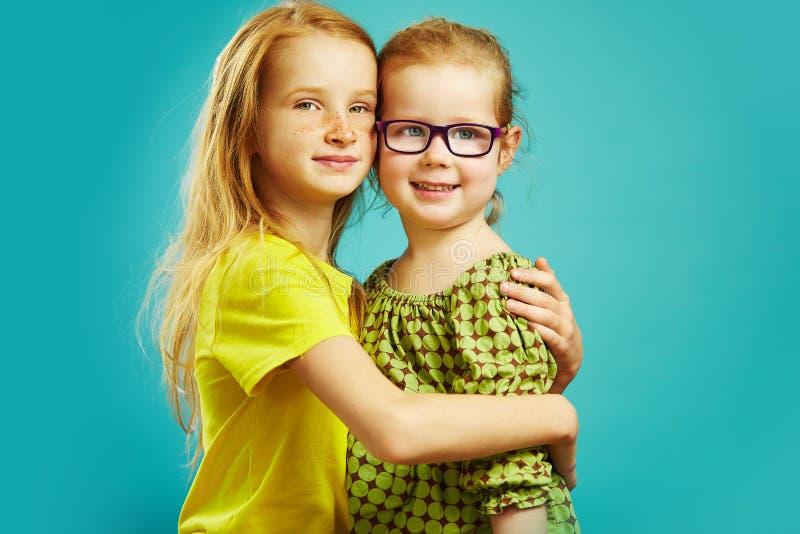 Η παλαιότερη redhead αδελφή δέκα έτη νεώτερη αγκαλιάζει τον ξάδελφο με τα θεάματα στοκ εικόνα