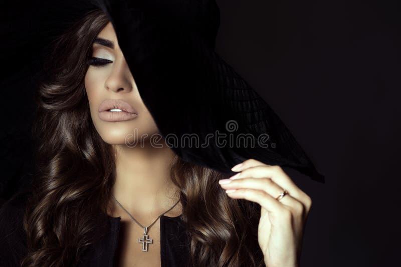 Η πανέμορφη γυναίκα με την άφθονη λάμποντας κυματιστή τρίχα και τέλειος αποτελεί το κρύψιμο του μισού του προσώπου της πίσω από τ στοκ φωτογραφία