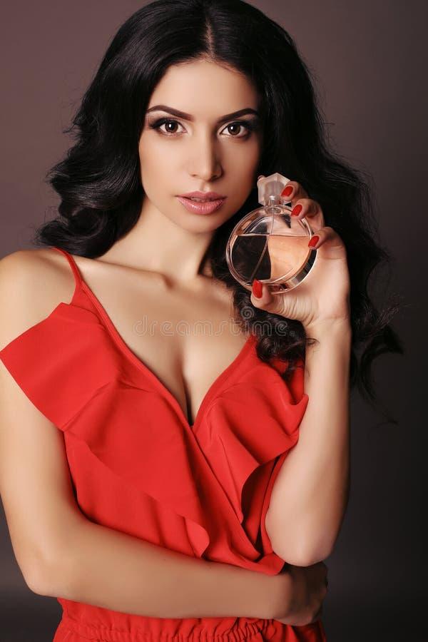 Η πανέμορφη γυναίκα φορά το κομψό κόκκινο φόρεμα, κρατώντας το μπουκάλι του αρώματος στοκ φωτογραφία