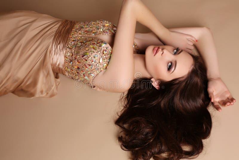 Η πανέμορφη νέα γυναίκα με τη σκοτεινή τρίχα και το βράδυ makeup, φορά το πολυτελές φόρεμα στοκ εικόνα